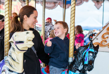 Foto op Aluminium Amusementspark Boy and Mother on Carousel Smiling at Each Other