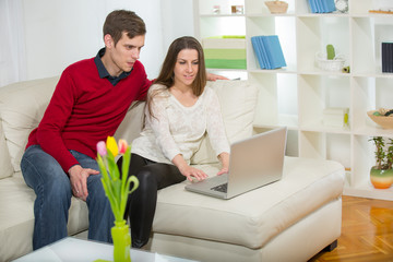 Young couple relaxing on sofa with laptop in the living room.Sel