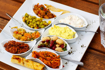 Differen appetizer and anti pasti on white plate in cafe or rest