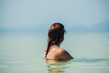 Woman sitting in water by beach