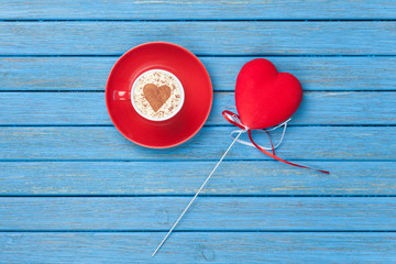 Cup of Cappuccino with heart shape symbol and toy