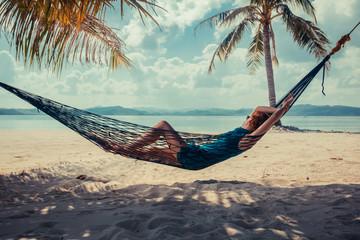 Woman relaxing in hammock on tropical beach