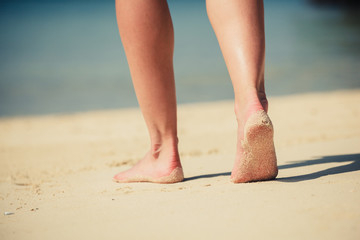 Feet of a young woman walking on the beach