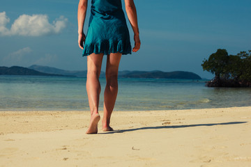 Young woman walking on tropical beach