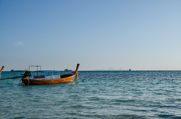 Wood boat on the blue sea