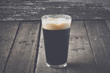 Pint of Dark Beer on Wood Background with Vintage Film Style