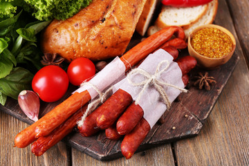 Assortment of thin sausages, bread, mustard in bowl and spices