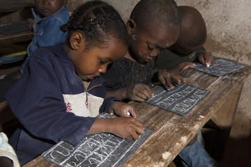des enfants écrivent sur une ardoise à MADAGASCAR