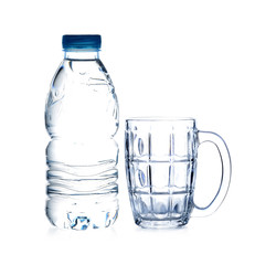 bottle of drinking water and empty glass on white background
