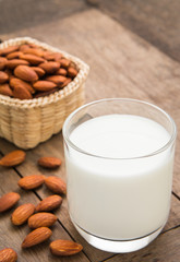 Almond milk in glass with almonds on wooden table