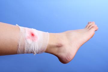 Wounded leg with bandage on blue background