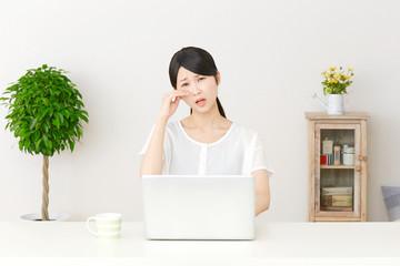 パソコンの前で泣く女性