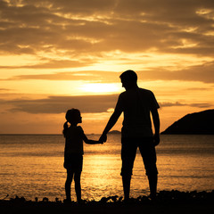 Father and daughter standing on the beach at the sunset time.
