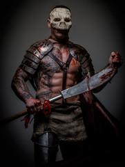 Gladiator in skull mask holds sword