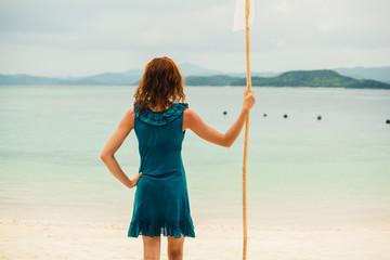 Woman on tropical beach with flag