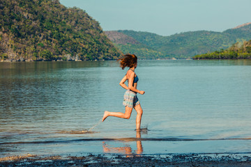 Woman running on tropical beach