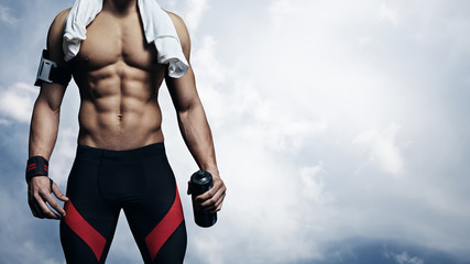 Strong athlete on blue sky background