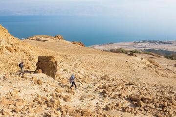 Couple walking desert trail down to Dead sea.