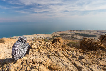 Wall Mural - Woman sitting desert mountain edge above sea.