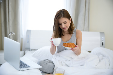 Smiling woman sitting on the bed with breakfast