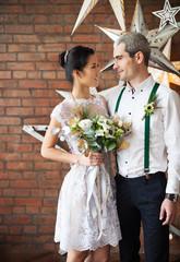 Cheerful married couple near the brick wall