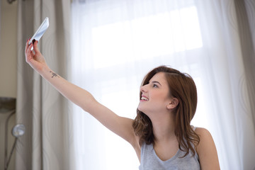 Young happy woman making selfie photo at home