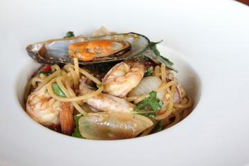 Thai syle spaghetti seafood in white dish.