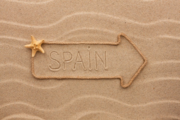 Arrow made of rope and sea shells with the word Spain on the san