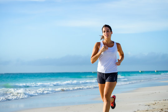 Sporty woman running at tropical beach