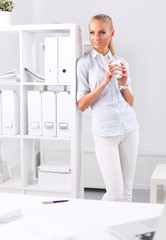 Young businesswoman standing near the desk with cup