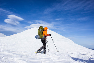 Winter hiking in the mountains on snowshoes .