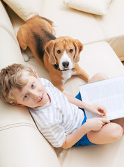 Boy reading tales for his dog at home