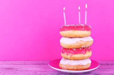 Delicious donuts with icing and birthday candles