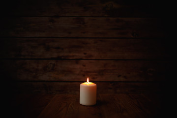 Candle on old wooden background