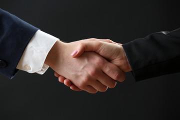 Business handshake on dark background