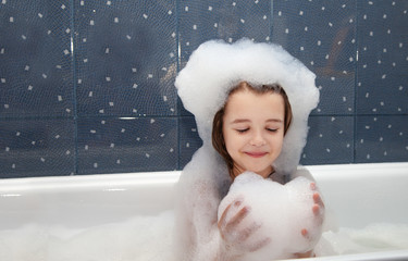 little girl playing with soap suds  in a bath