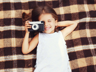 Funny child shooting vintage old retro camera and having fun on