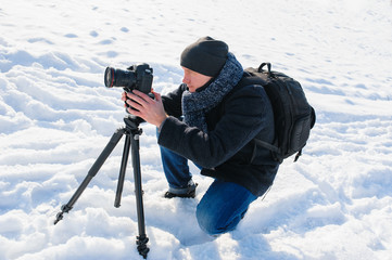 male photographer with a tripod in winter
