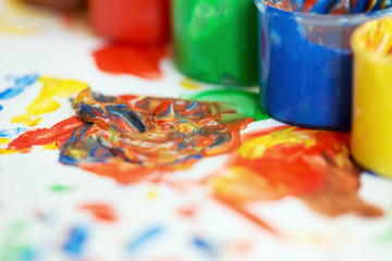 Jars of finger paint on a painting