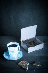 Cup of coffee, biscuits and a box of cigarettes on old wooden ta