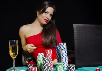 Portrait of beautiful girl in red dress playing poker online