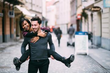 Young man giving girlfirend piggyback ride
