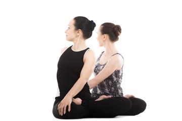 Two Yogi female partners sitting in yoga Lotus Pose