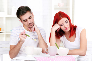 Sleepy couple has breakfast in kitchen
