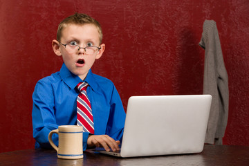 Young frightened boy on working on computer.