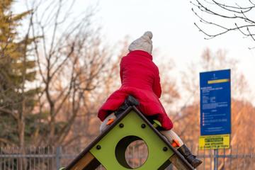 red coat jacket playground kids