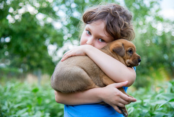 Little girl with a puppy in her arms