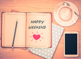 Happy Weekend on notebook , pencil, smart phone and coffee cup w