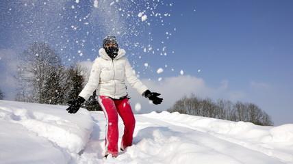 junge Frau freut sich über Neuschnee