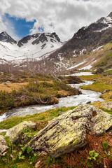 View to snow on Caucasus mountains over clear water stream near